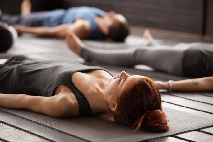 Group Of Young Sporty People Practicing Yoga Lesson Lying In Dea